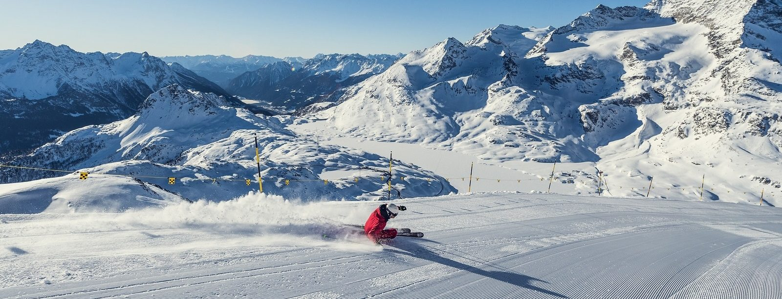 Skier carving, with the snow-covered Lago Bianco and the Poschiavo valley in the background.