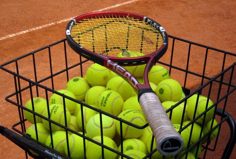 Korb mit Tennisbällen und Schläger