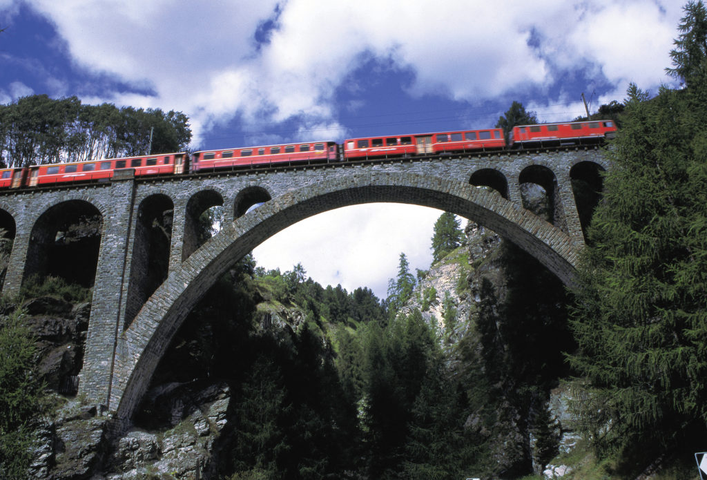 Rhaetian Railway/RhB - The train crosses the river on a 110 metre-wide viaduct on its way out of the valley of Val Tuoi, shortly before the station at Guarda in the Lower Engadin region.